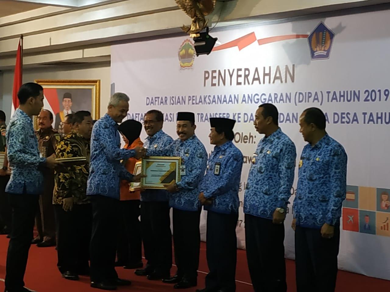 Ganjar Pranowo menyerahkan pengharagaan ke Bupati Pati Haryanto. (istimewa)